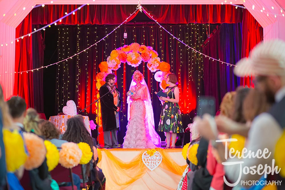 Bride smiling on the stage along with groom