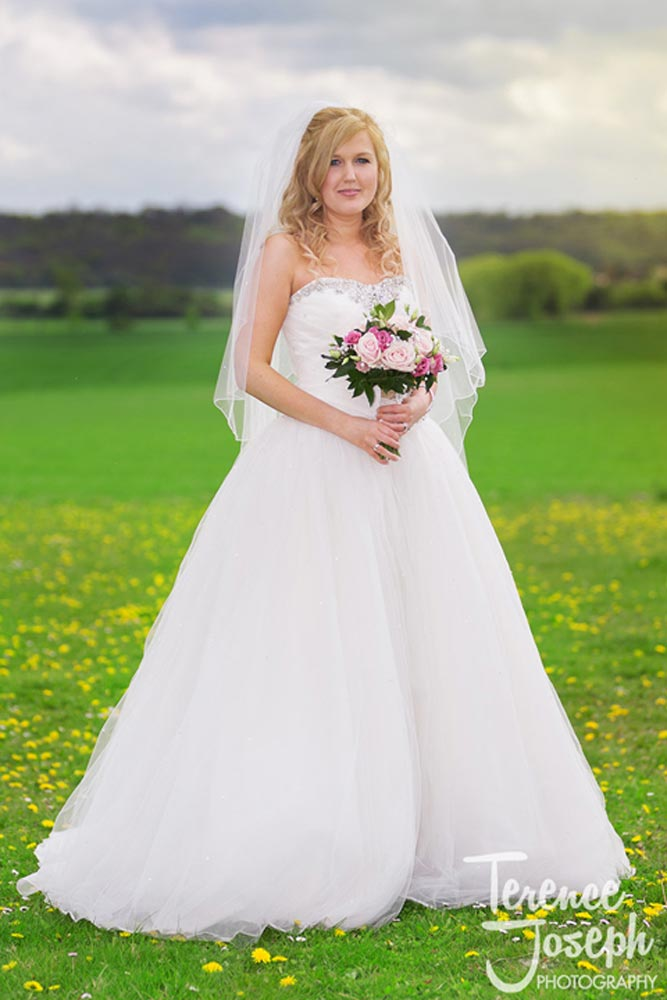 Lovely bride in a wedding dress standing in a field