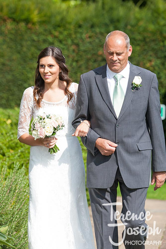 Brides walk down the aisle with father at outdoor wedding at Oakwood House in Maidstone