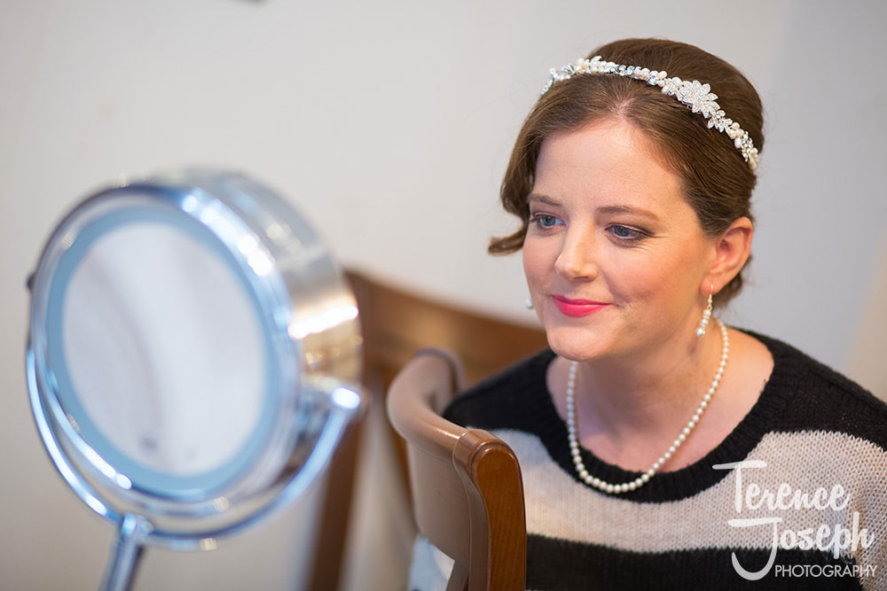 Bride looking into the mirror after getting ready photos by Terence Joseph Photography