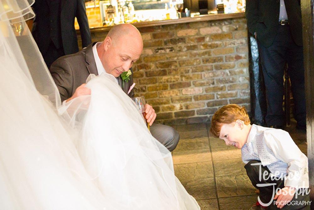 Cheeky boy looks under bride's wedding dress