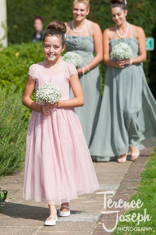 Bridesmaid walks to outdoor wedding at Oakwood House in Maidstone
