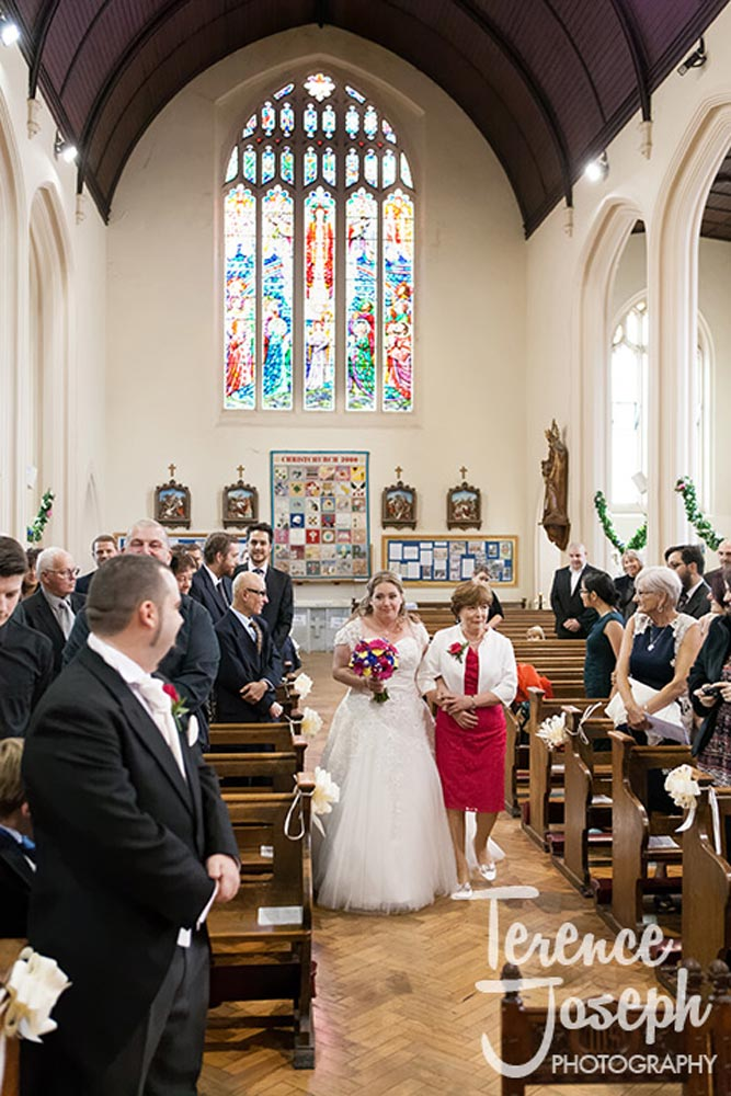 The bride and her mum walks down the aisle at Christ Church London Wedding