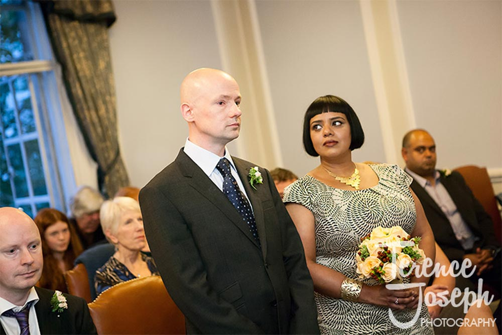 Bride lovingly looks at groom during London wedding ceremony