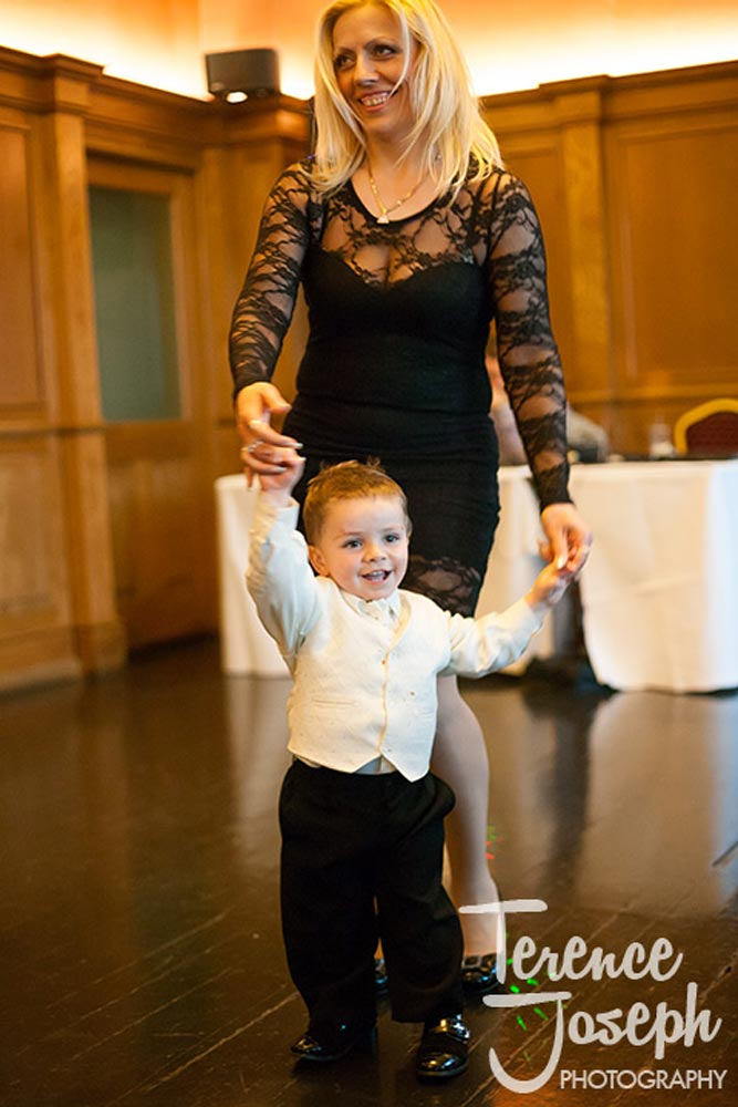 Young child dances with mother at wedding reception