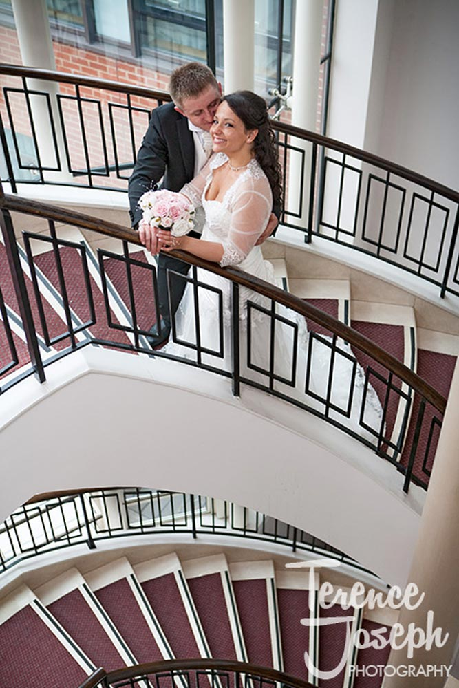 Bride kissed by groom on stairs of Hotel London