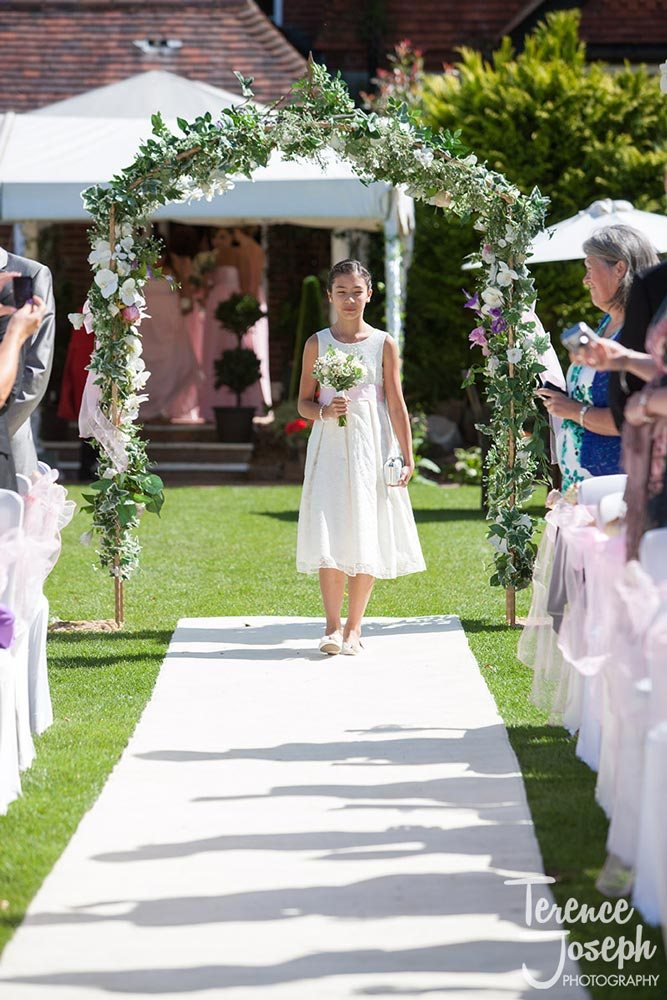 The first bridesmaid walks down the summer aisle