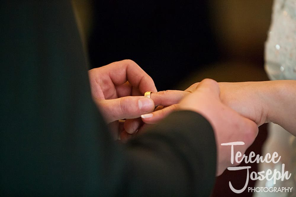 Elegant ring placed on brides third finger during ceremony in London
