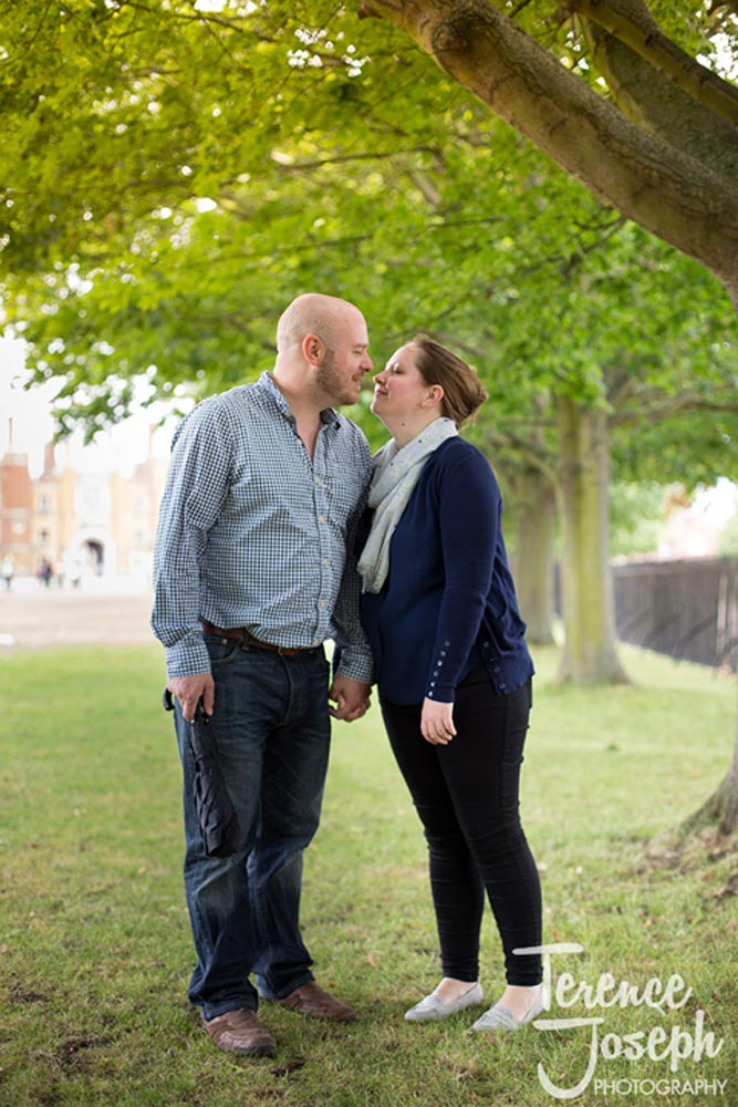 Cute couple about to kiss under a tree in Hampton Court