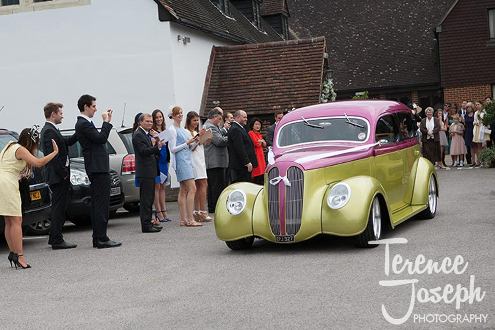 The bride and groom leave in their hotrod wedding car