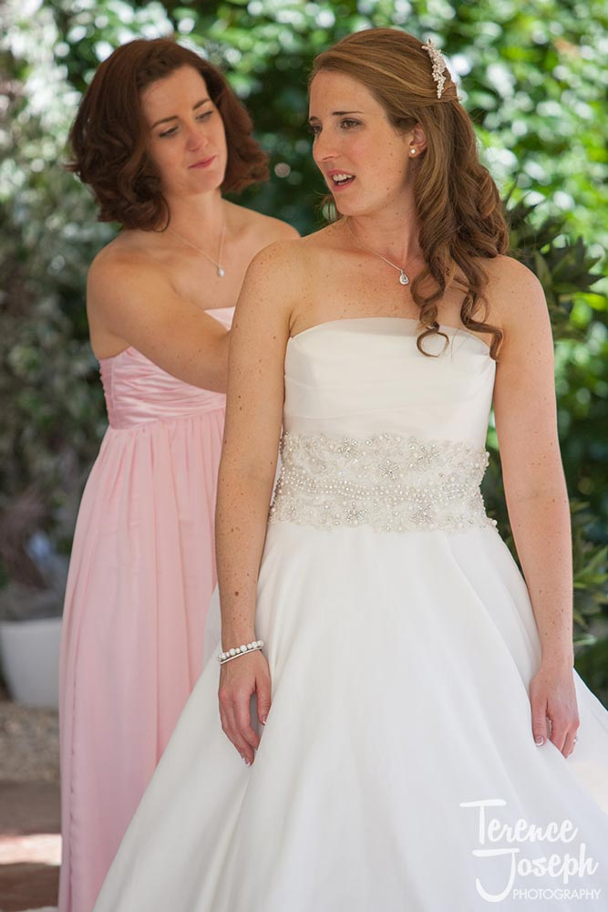 Sister of the bride helps with her wedding dress