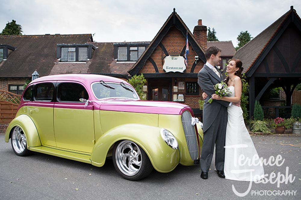 Couple photo with their hotrod wedding car