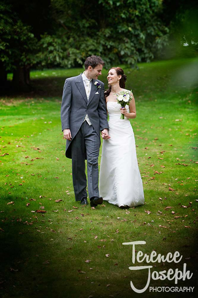 Mr and Mrs walk hand in hand through a park