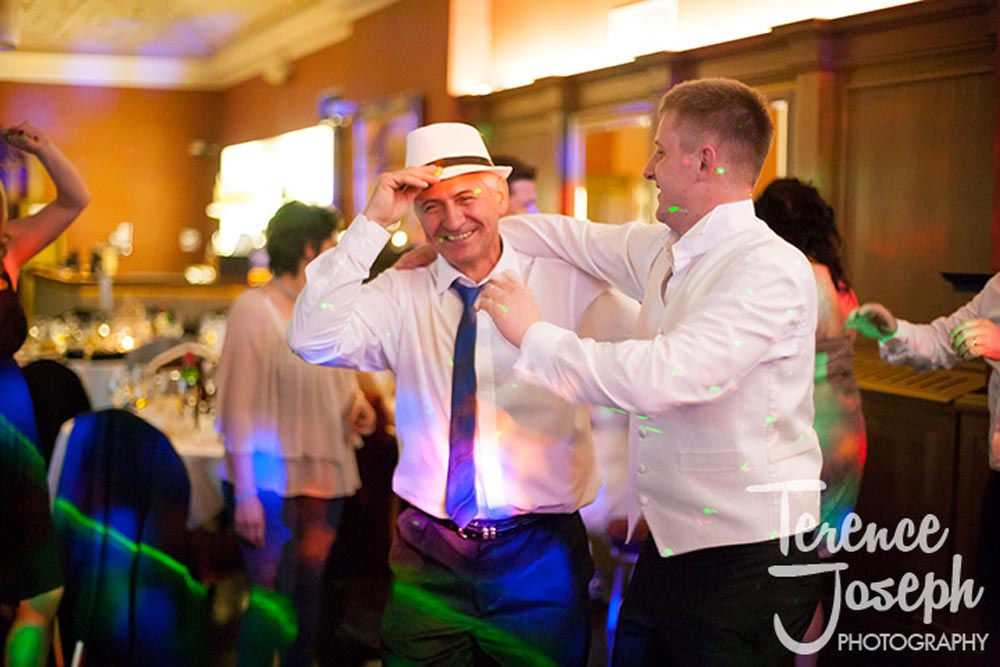 Groom and father laugh during wedding reception in London