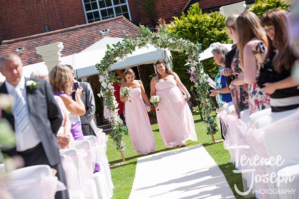 Bridesmaid in pink dresses walk down the aisle on this Summer's day
